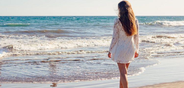 A bride walking towards the sea.