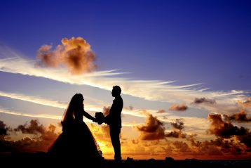 A bridal couple in silhouette in front of a sunset.