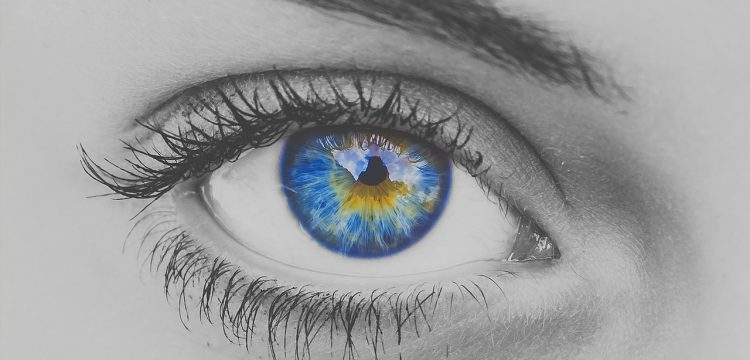 A black and white photo of a woman's eye with the pupil multi-colored.
