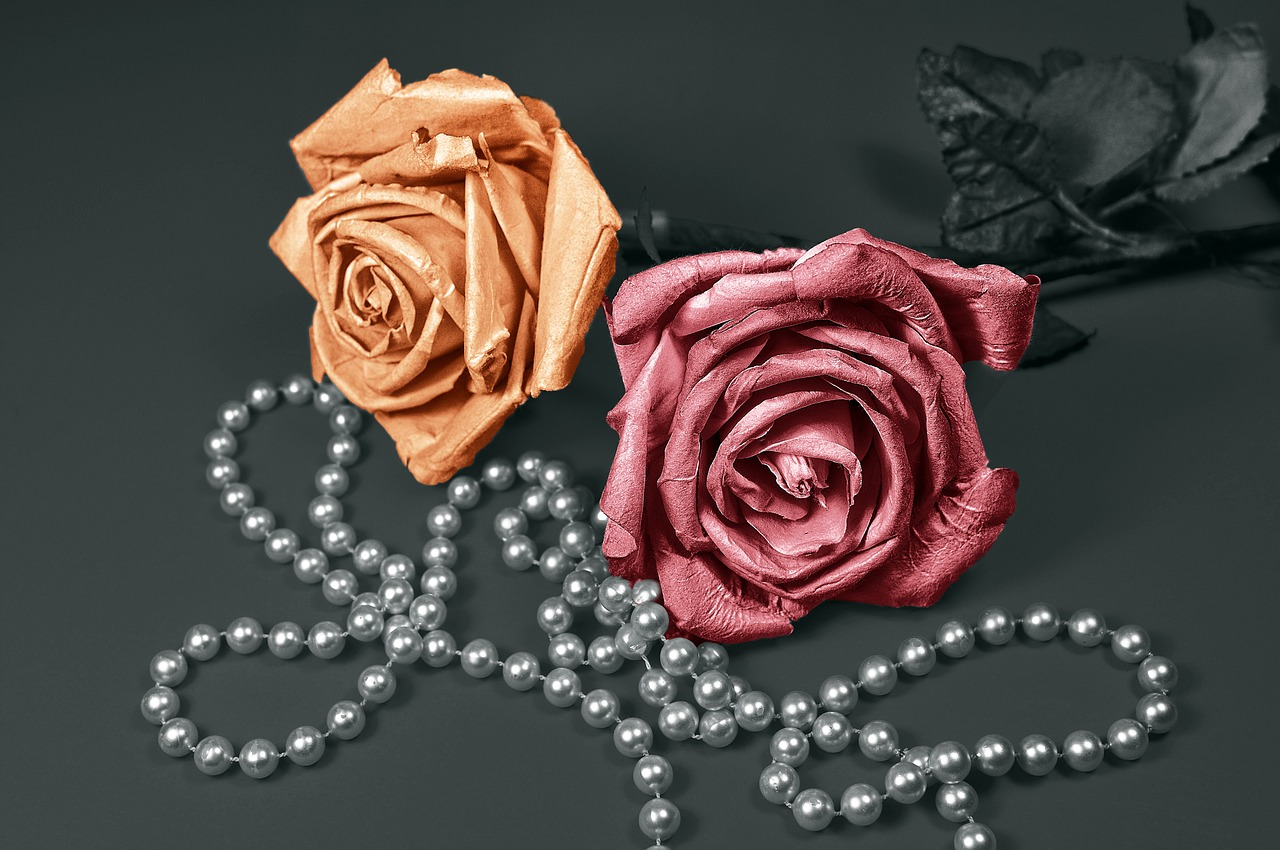 Two roses with a strand of pearls.