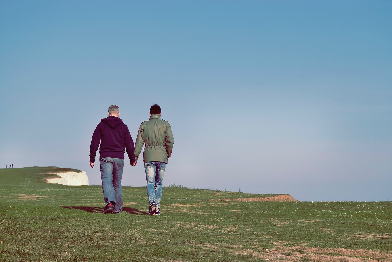 Two men walking hand in hand at a scenic location.