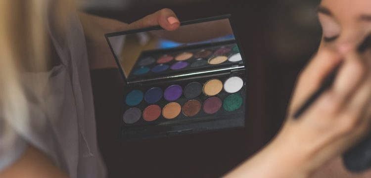 A makeup artist holding an eyeshadow palette and applying the shadow to a woman.