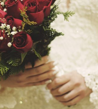 Torso shot of a bride holding red roses and baby's breath.