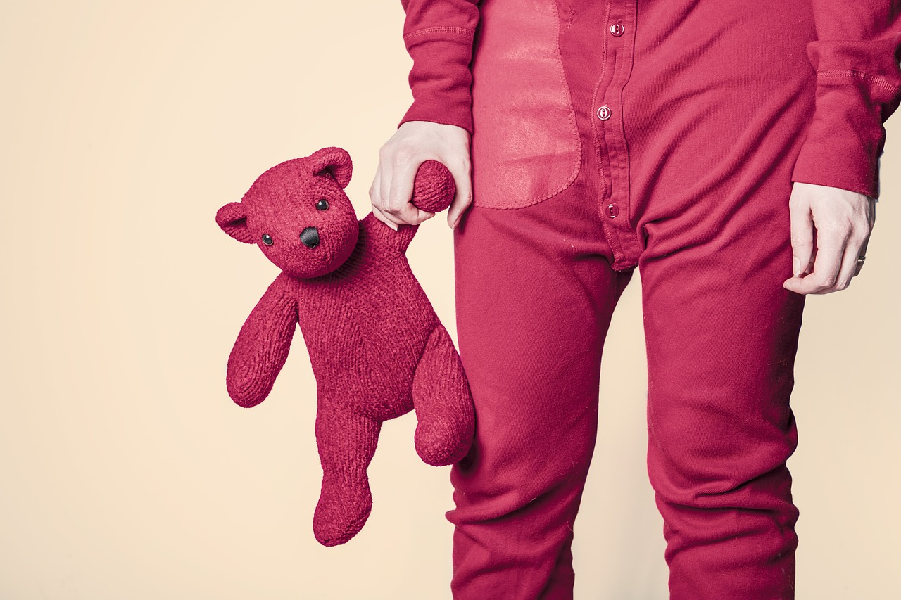Person in red pajamas holding a red teddy bear.