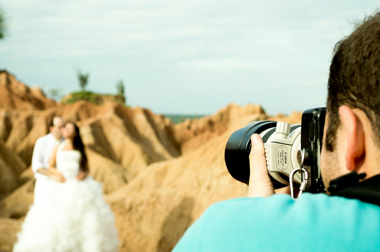 Photographer taking a picture of a married couple.