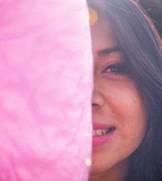 A woman partially hiding behind pink cotton candy.