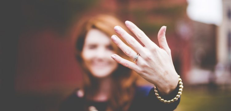 Woman holding up her hand with a diamond ring on it.