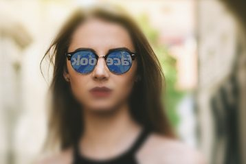 A woman with the Facebook logo reflected in her sun glasses.