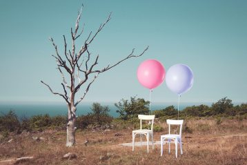 Pink and purple balloons tied to white chairs.
