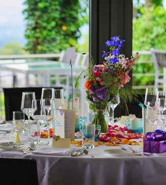 Beautifully set table with bright flowers and full tableware.
