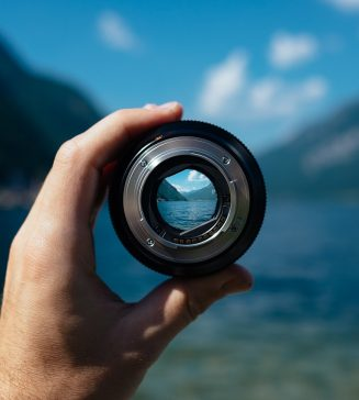 A hand holding up a lens with a view through it to beautiful mountains.