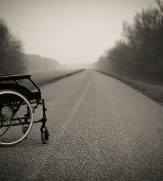 Black and white photo of a wheelchair sitting on an empty road.