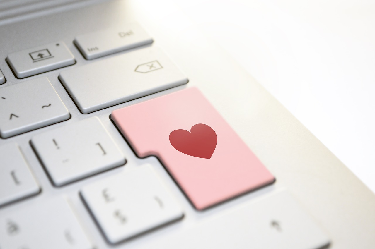 Computer keyboard with a heart on one of the keys.