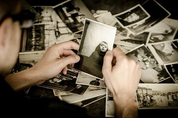 Someone looking through piles of photographs.