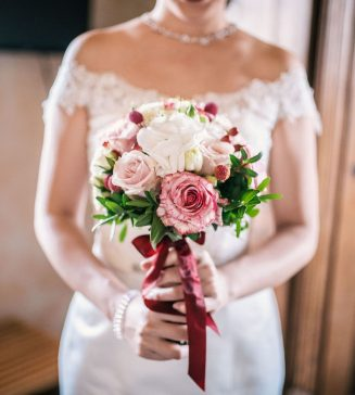 Bride holding a red, white, and pink bouquet.