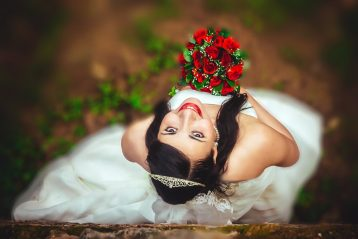 A bride holding a bouquet of red flowers looking upwards at the camera.