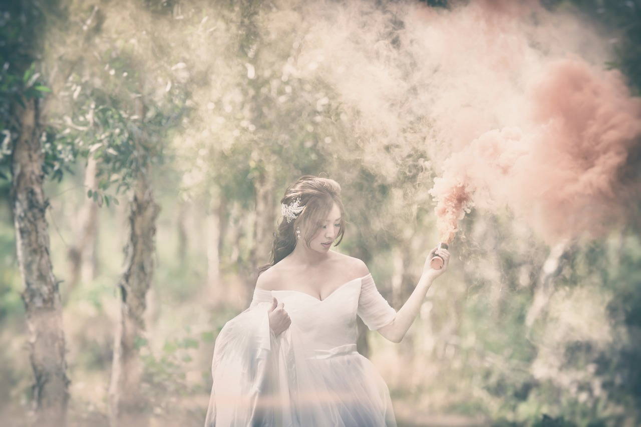 Bride walking through a field or forest.