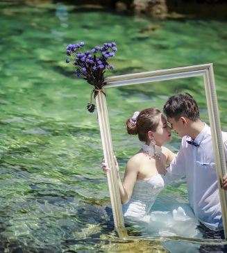 Bride and groom standing in a stream.