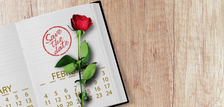 """A """"save the date"""" notebook with a rose in it."""