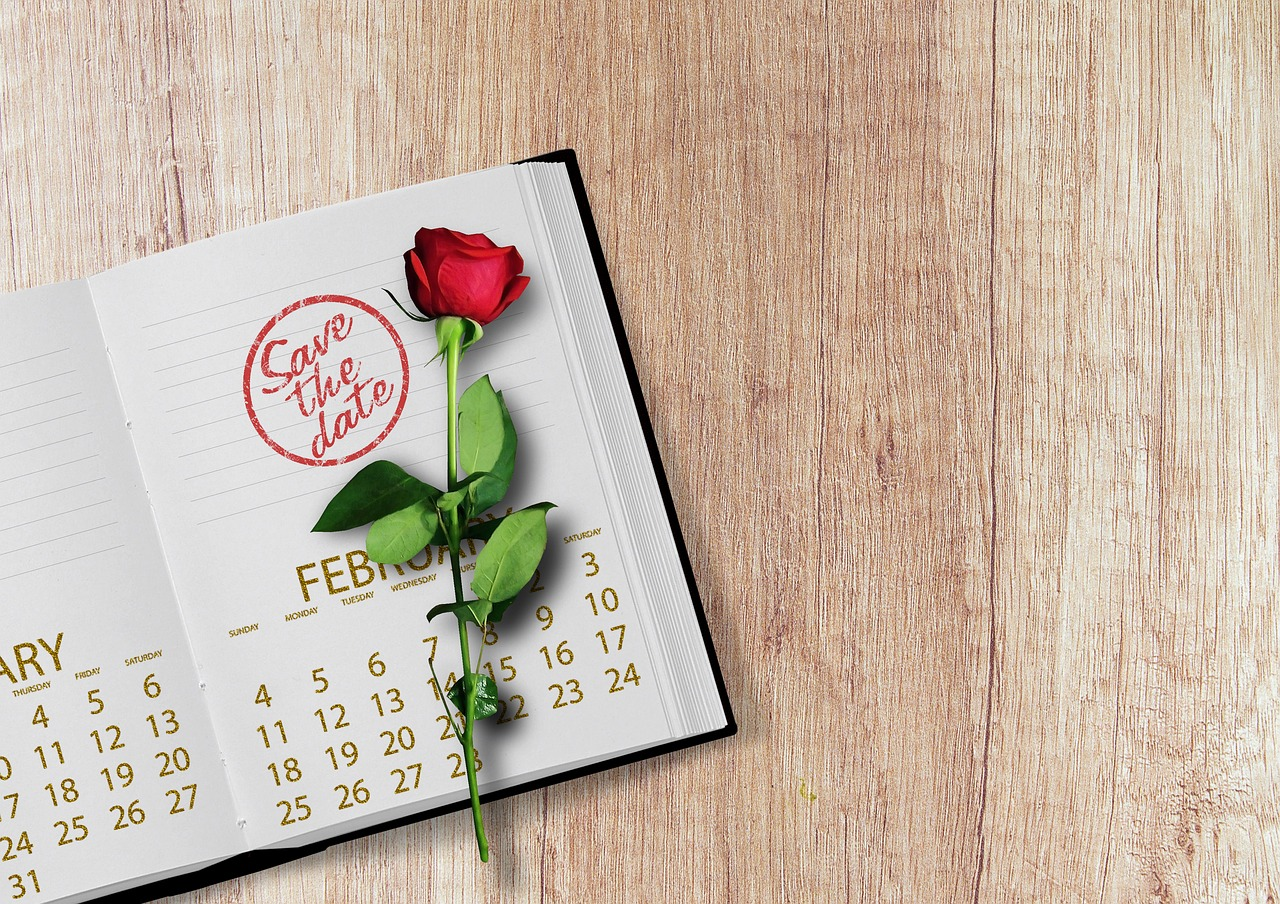 "A ""save the date"" notebook with a rose in it."