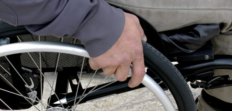 Close up of man grabbing wheelchair wheel.