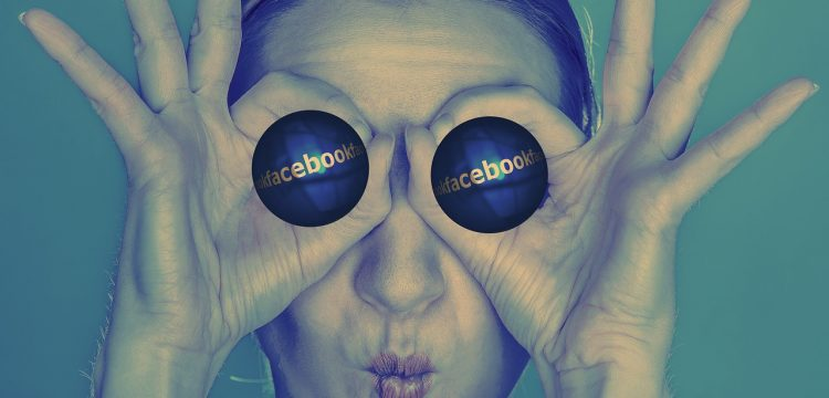 Person holding two cylindrical objects in front of her eyes that have the Facebook logo on them.