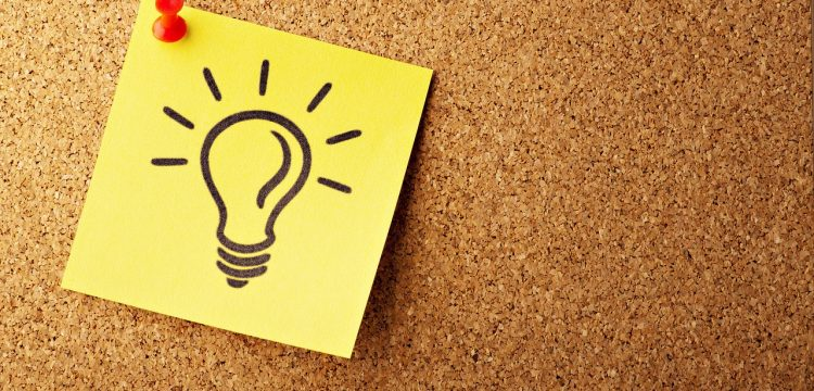 """A sticky note with a light bulb on it to denote the word """"idea""""."""