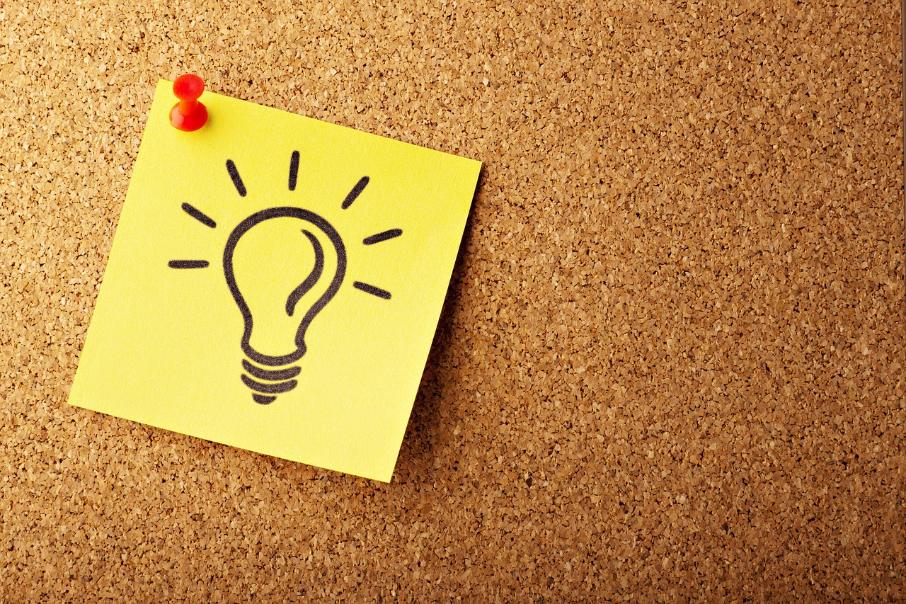 "A sticky note with a light bulb on it to denote the word ""idea""."