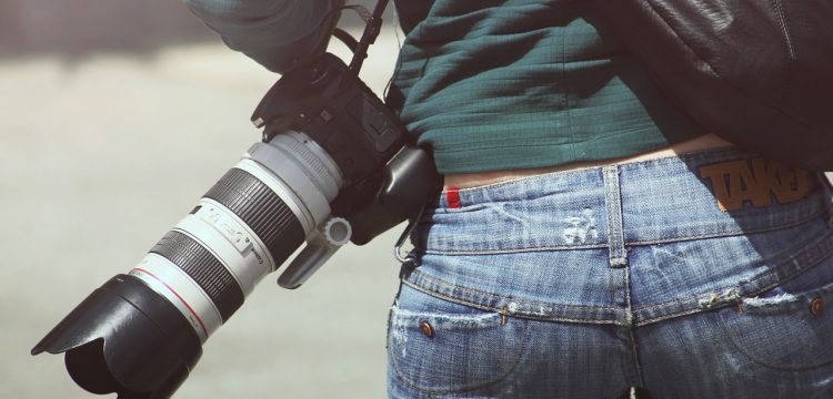 Person walking with a professional camera.