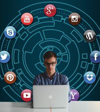 Man sitting at a laptop with various social media icons surrounding him.