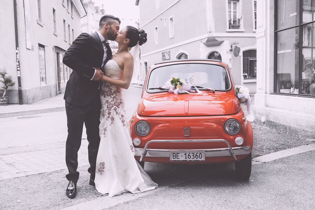 Bride and groom kissing by an orange sports car.