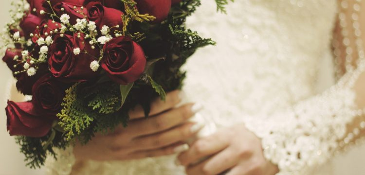 Bride holding red roses.