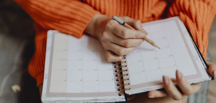 A person writing in a calendar notebook.