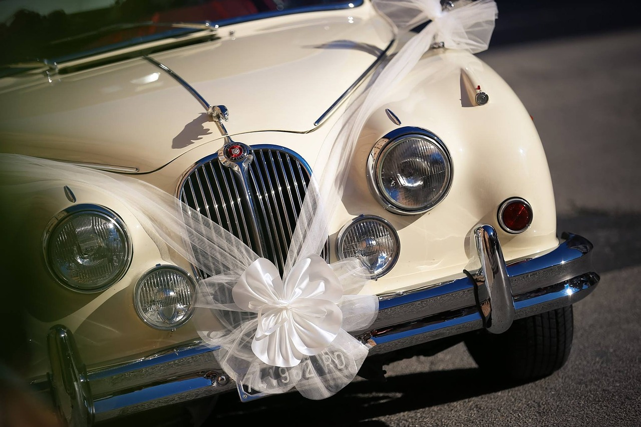 A luxury car with a white ribbon and bow made of tulle draped on it.