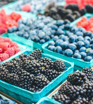 Rows of blueberries and raspberries at a farmers' market.