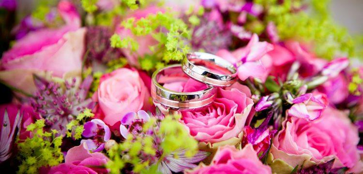 Wedding bands on top of wedding flowers.