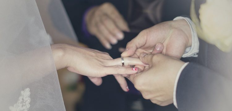 Groom putting ring on bride's finger.