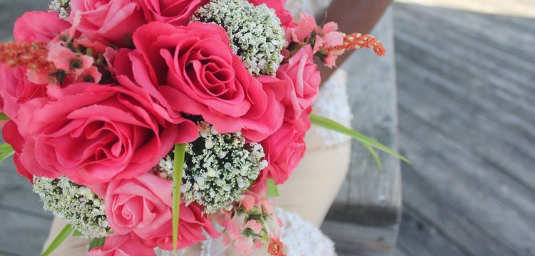 Bride holding a bright pink bouquet of flowers.