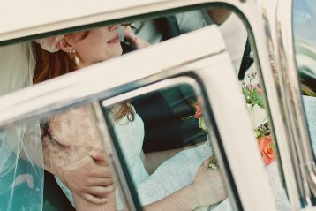 Bride and groom in vintage car.