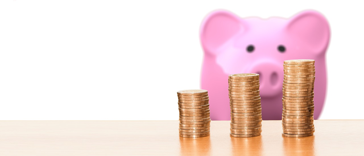 A pink piggy bank with coins in front of it.