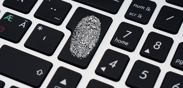 A thumb print on a computer keyboard.