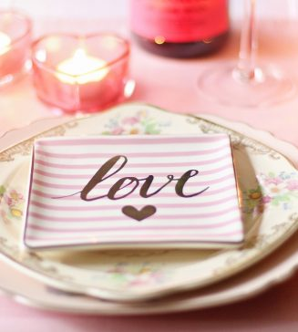 """A place setting for a wedding with the word """"love"""" on a plate."""
