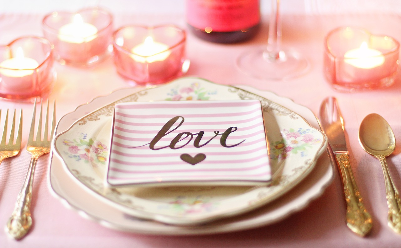 "A place setting for a wedding with the word ""love"" on a plate."