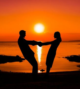 Couple holding hands at sunset on a beach.