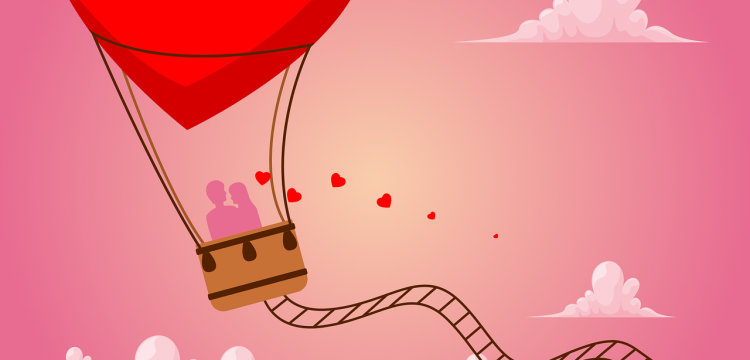 Couple riding in a hot air balloon shaped like a heart.