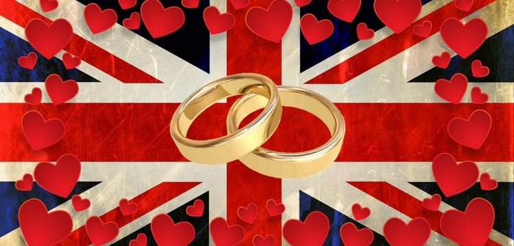 Wedding bands surrounded by hearts and lying on a British flag.