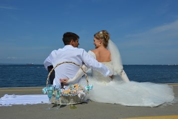 Bride and groom on beach with glasses of champagne.