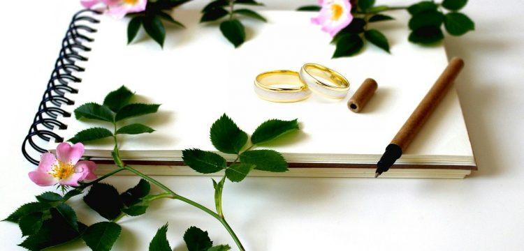 Wedding rings with flowers around it.