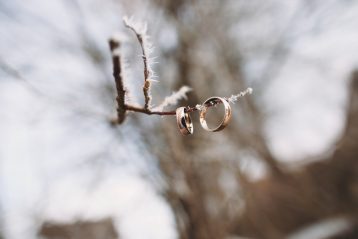 Wedding rings hanging on an icy branch.