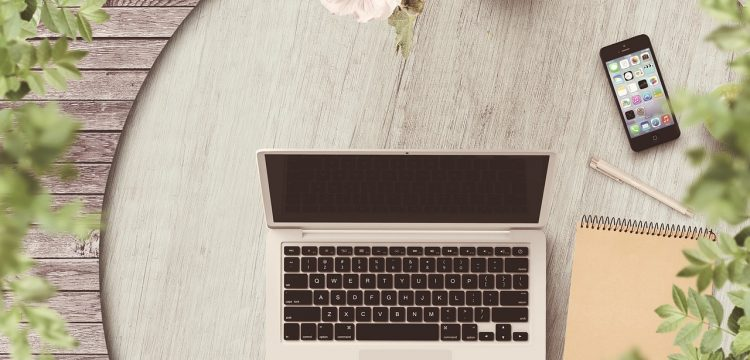 Laptop, cell phone, and flowers.